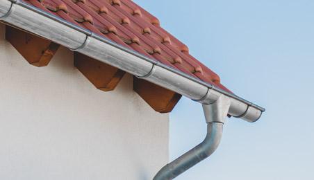 Gouttière et descente en zinc au bord d'un toit en tuile rouge