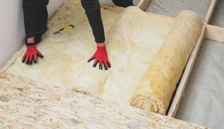 Ouvrier installant de la laine minérale au sol