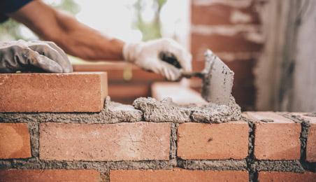 Ouvrier construisant un mur en briques avec du ciment