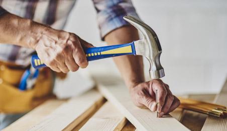 Artisan plantant un clou avec un marteau de menuisier