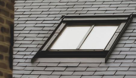 Fenêtre de toit à meneau sur un toit ancien en ardoise