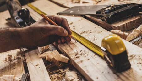 Menuisier prenant une mesure sur une planche avec un mètre ruban