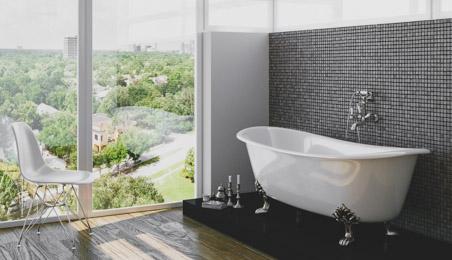 Salle de bain avec baignoire sur pied devant un mur en mosaîque grise