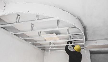 Plâtrier posant une ossature en quart de cercle sur un plafond