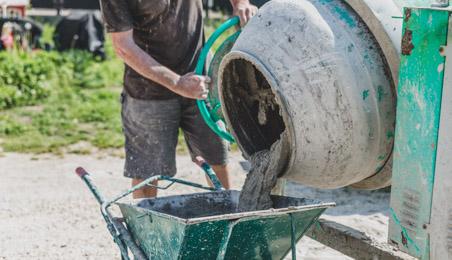 Ouvrier versant du béton depuis une bétonnière