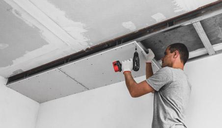 Plaquiste posant une plaque au plafond avec une visseuse