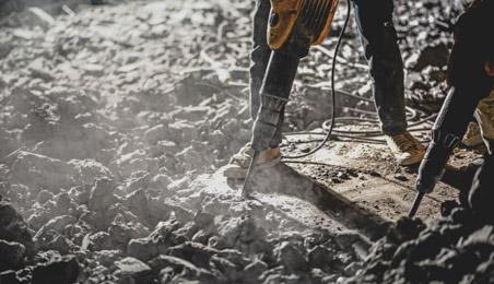 Ouvrier cassant un sol avec un marteau piqueur