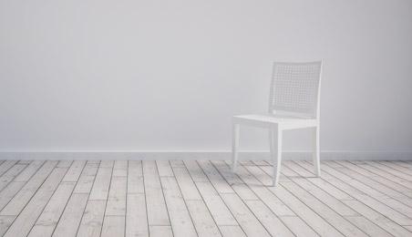 Parquet en bois blanchi avec un mur blanc en fond et une chaise blanche