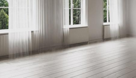 Parquet en bois blanchi dans une pièce avec trois fenêtres