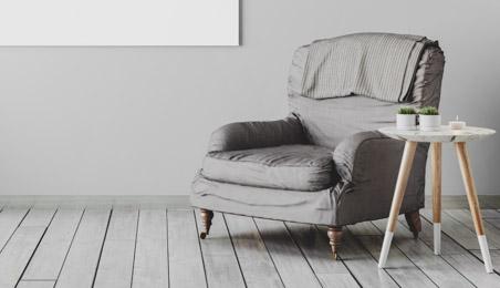 Parquet gris avec un fauteuil gris et une petite table blanche