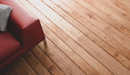 Sol en parquet naturel avec coin de canapé en cuir rouge