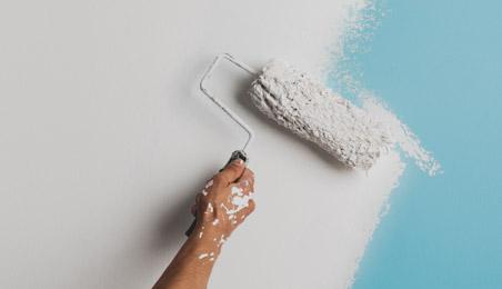 Peinture blanche étalée au rouleau sur un mur bleu