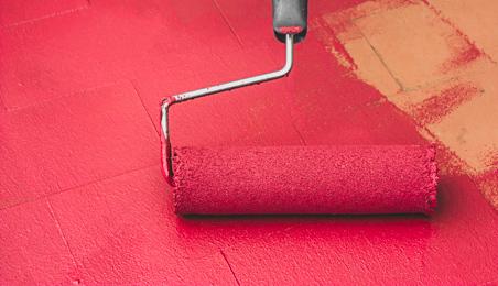 Peinture rouge passée au rouleau sur un sol