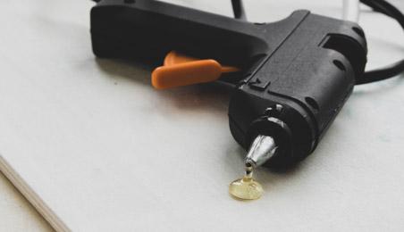 Pistolet à colle posé sur le sol avec une goutte de colle