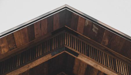 Planches de rive en bois foncé sur un chalet en bois