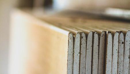 Plaques de plâtre avec pellicule de papier brun posées sur la tranche