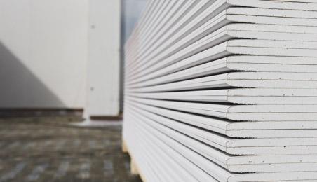 Pile de plaques de plâtre standard sur un plancher foncé