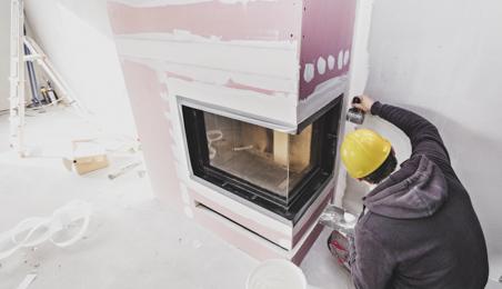 Plâtrier finissant les joints sur un insert habillé de plaques feu