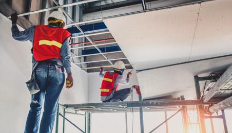 Ouvriers fixant des plaques de plâtre au plafond
