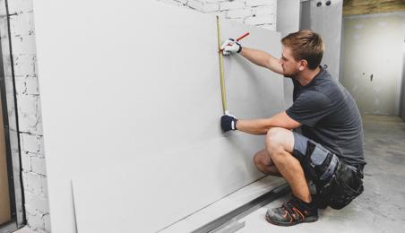 Ouvrier découpant une plaque pré-peinte blanche