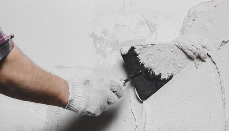 Main d'un ouvrier étalant un enduit sur un mur blanc avec une truelle