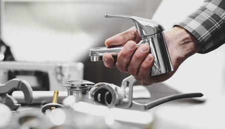 Robinet chromé dans la main d'un artisan, ensemble de robinets et pièces posés sur une table