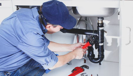 Plombier intervenant sur un siphon dans un meuble de cuisine blanc