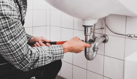 Plombier intervenant sur un siphon chromé sous un lavabo de salle de bains