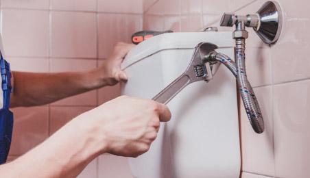 Plombier raccordant un tuyau d'alimentation d'eau à un réservoir de chasse d'eau