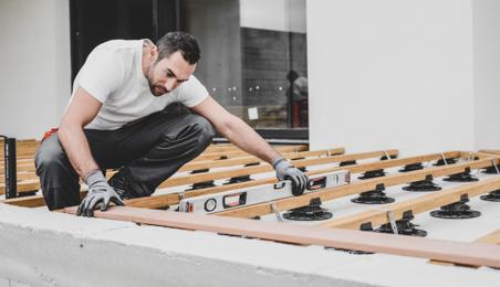 Ouvrier installant des traverses de terrasse en bois sur des plots