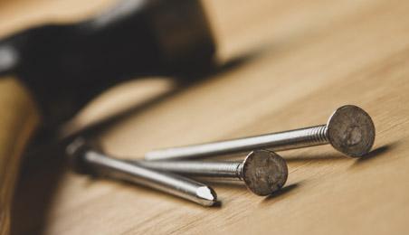 Clous en acier avec marteau en arrière plan