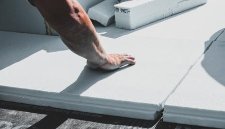 Ouvrier posant une dalle de polystyrène expansé au sol