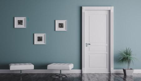 Porte d'intérieur blanche sur un mur bleu, canapé blanc
