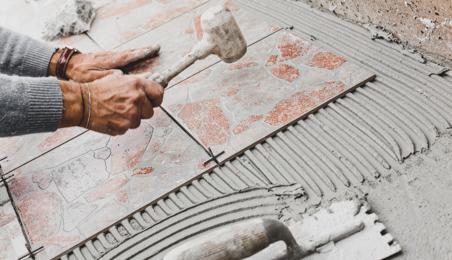 Carreleur posant une dalle de terrasse sur de la colle à carrelage