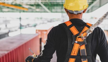 Ouvrier de dos portant un harnais de sécurité et un casque