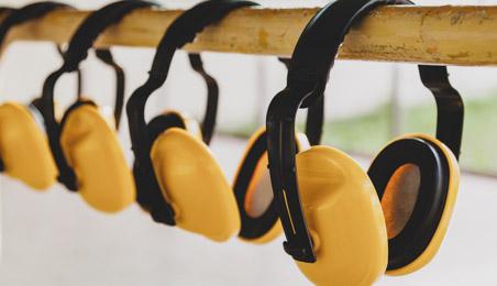 Casques anti-bruit jaune suspendus sur une barre en bois