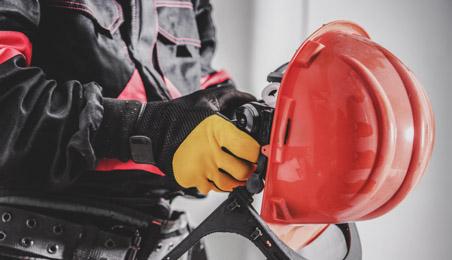 Ouvrier tenant un casque de chantier rouge avec visière