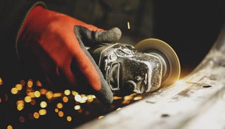 Zingueur découpant une plaque portant des gants de protection rouge
