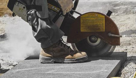 Ouvrier portant des chaussures de protection et genouillère découpant une dalle avec une scie de chantier