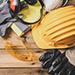 Casque de chantier jaune, gants, lunettes de protection sur une table en bois