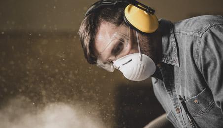 Ouvrier travaillant dans un environnement poussiéreux portant un masque et un casque anti-bruit