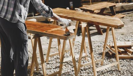 Ouvrier passant de la lasure sur une planche posée sur un tréteau en bois