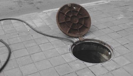 Regard de voirie ouvert avec un tuyau qui en sort