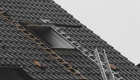 Velux en cours de remplacement sur un toit en tuiles plates marrons