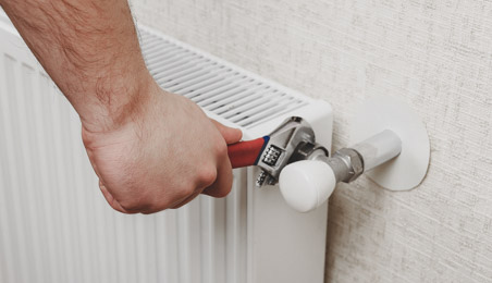 Plombier fixant une tête de radiateur