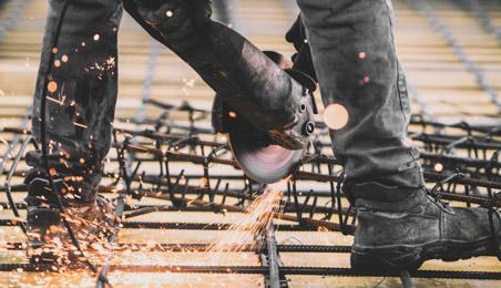 Ouvrier découpant un treillis soudé avec une scie de chantier