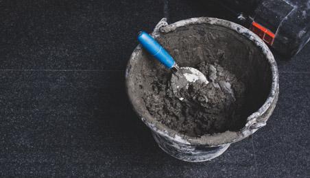 Seau en PVC noir contenant du mortier et une truelle