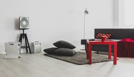Salon moderne avec sol PVC décor bois blanchi, tapis gris, table basse rouge, enceinte sur pied blanche dans le fond de la pièce