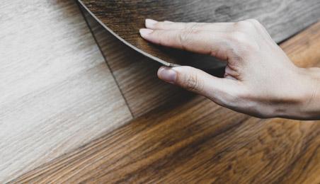 Lames de sol PVC de teinte bois naturel, un coin soulevé par une main