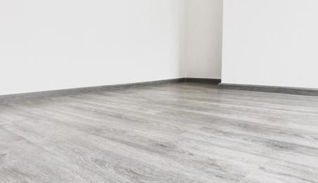 Angle de pièce sol stratifié teinte bois blanchi et murs blancs